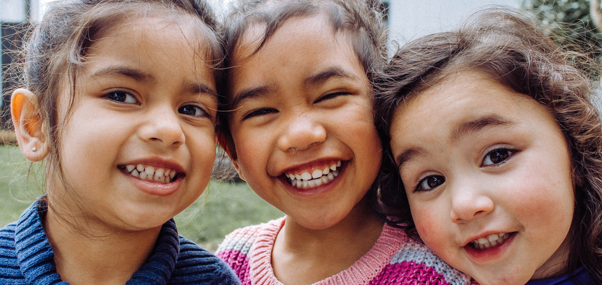Three happy, smiling kids with their heads together.